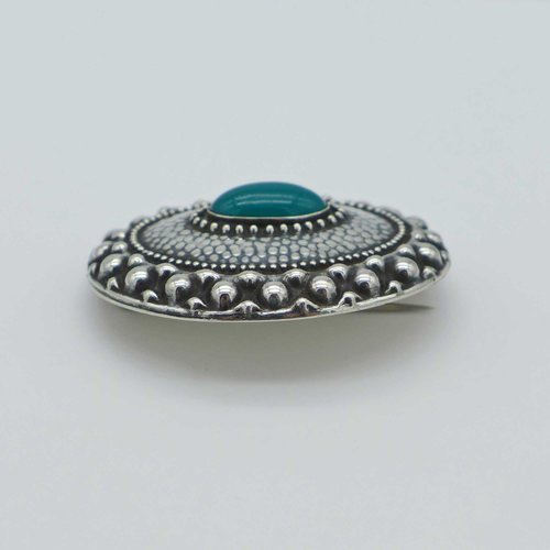 Geared silver brooch with green paste